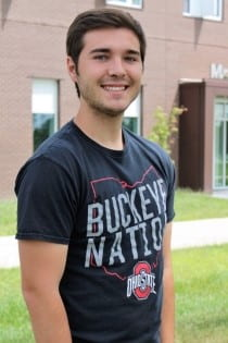 Zach Sparks stands at The Ohio State University at Newark smiling in front of McConnell Hall