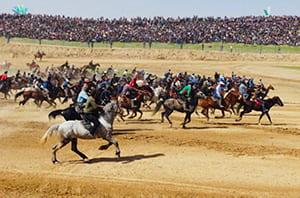 Horsemen running across a dirt field