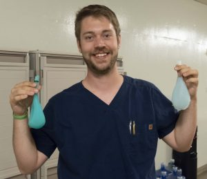Summer Assistant Marshall Aanestad holding two prototype silicone bladders being developed for the Clinical and Professional Skills Lab.