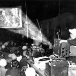 Man operating film projector in front of audience