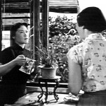 Woman watering plant and talking to other woman