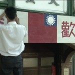 An actor playing a young man putting up a sign to welcome the arrival of the Nationalist soldiers in the documentary Scars of 2/28