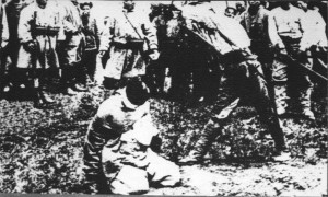 Crowd gathered around blindfolded man kneeling on ground for execution