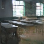 Desks in a classroom as seen through a window