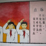 Mural of three obedient children with slogans written to the right of them