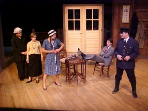 "Fig. 3: A crossed-dressed maid in the otherwise gender-appropriate cast of ""Oppression."" From left, Loren Vandegrift as the maid, Christa Brelsford as the landlady, Chloë Demrovsky as the female guest, John William Schiffbauer as the male guest, and Christopher R. Hildebrand as the policeman."
