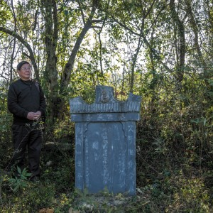 Tan Hecheng at a tombstone put up by Zhou Qun for her husband and three children, who were among the thousands of people killed during the Cultural Revolution in Dao County, southern China, November 2016; photograph by Sim Chi Yin