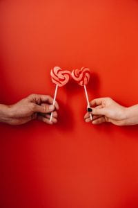 two hands holding heart-shaped lollipops on red background