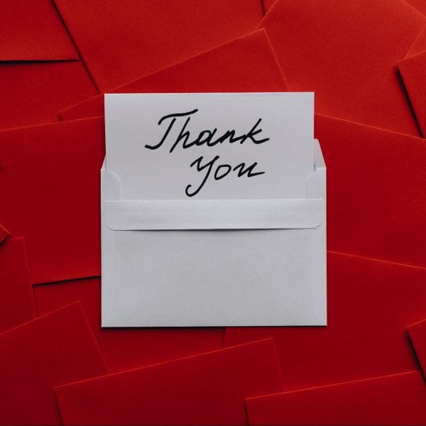 handwritten thank-you card with red envelops in background