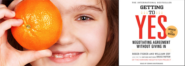 Female child holding an orange over her right eye and smiling, juxtaposed next to the cover of the book Getting To Yes