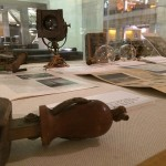 Artifacts in a showcase; cameras, bulbs, and literature explaining their significance.