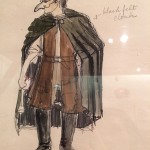 Costume sketch of a man with upper half mask with long nose. Black cape and shoes, brown jacket.
