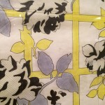 close up shot of a sketch of yellow grid with black white and gray leafy rose bush growing on it