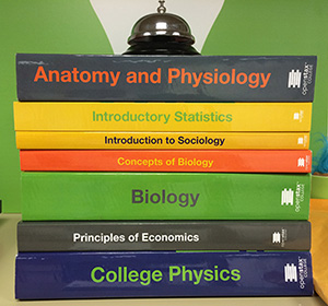 Stack of print textbooks from openstax