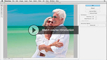 Image open in Photoshop window. Image is of a mature couple laughing and holding each other at a beach with white sands fading into green water and sunny blue sky.