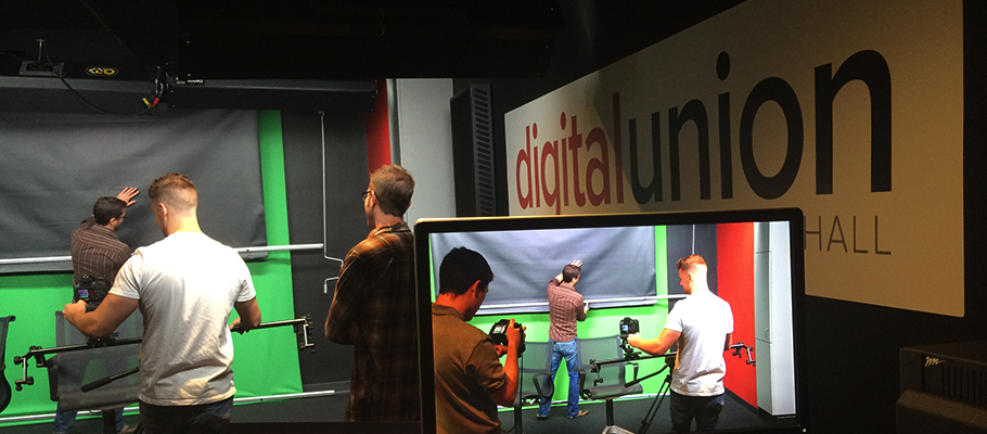 Three student workers at Digital Union Denney Hall video recording studio. Students are shown smoothing out the backdrop and using various camera equipment.