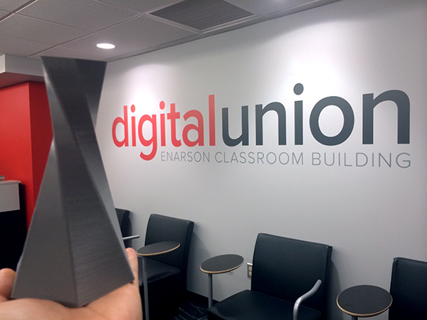 Gray 3d printed vase; very angular. In the background is a word mark on the wall that reads Digital Union, Enarson Classrooms Building.