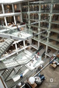 Inside of Thompson Library at OSU. Photo features a staircase overlooking a main floor and several stories of the building with glass walls.