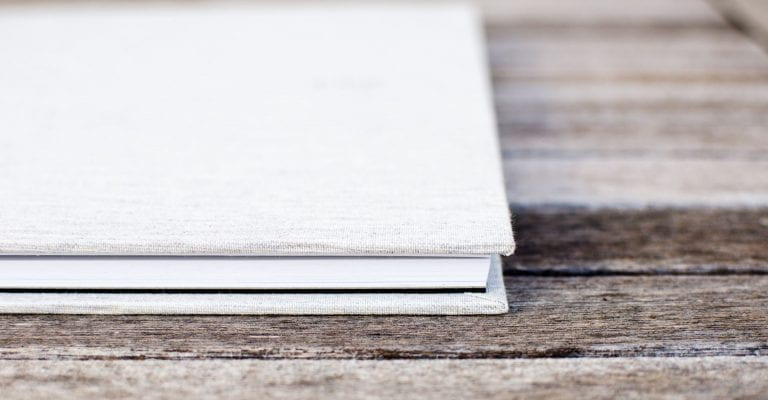 white notebook on wood table