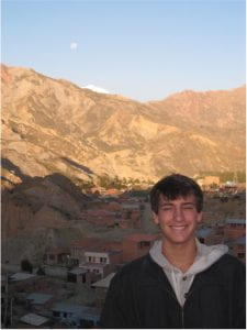 Portrait of Micah smiling in front of a mountainous landscape.
