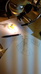 A wasp under a microscope with a sketch of the wasp larger in front of it