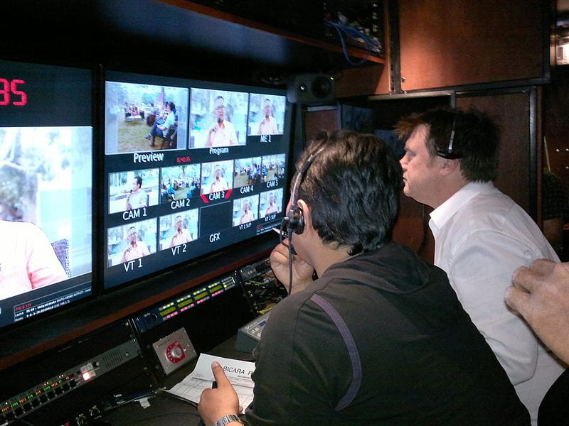Producer in a control room with a director while he directs a program