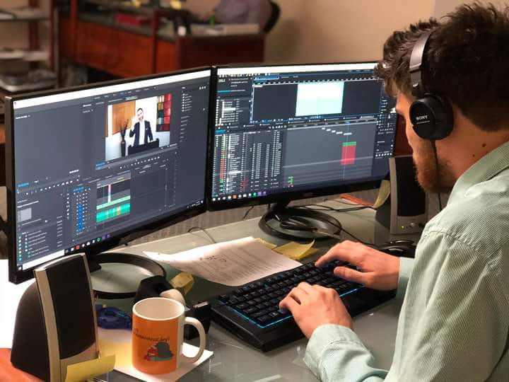 Person on computer with headphones performing non- linear editing