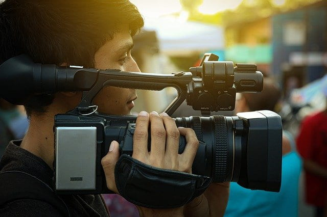 young male holding video camcorder on right shoulder looking through viewfinder