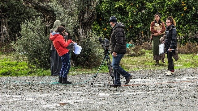 Group of five people on a video shoot while one of them directs