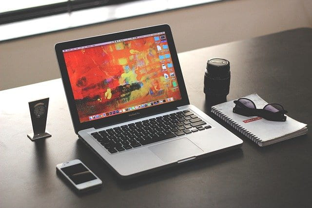 small laptop computer next to iPhone, camera lense, notepad, glasses and clock