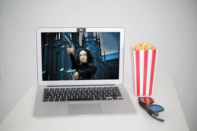 Laptop display a video image with popcorn and sun glasses next to it