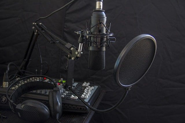 Professional studio microphone set-up with headphones, mic screen and mixing board and microphone