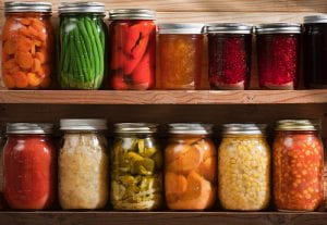 Subject: Two wooden shelves holding a variety of canned vegetables and fruits, lined up in rows of glass jars. Food staples canned include jellies, sauces, or slices of carrots, green beans, tomatoes, corn, sweet potatoes, sauerkraut, roasted red peppers, dill pickles, raspberry jam, orange marmalade, grape jelly, and a tomato and corn soup.