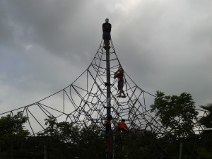 My friends climbing a rope tower.