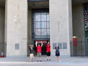 Four students stand in front of the Ohio Stadium football stadium and it's red and white Block O stained glass window. The individuals are spelling out OHIO with their arms.