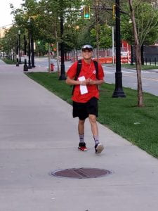 Young man in red Ohio State shirt walking down the sidewalk with a big smile on his face.