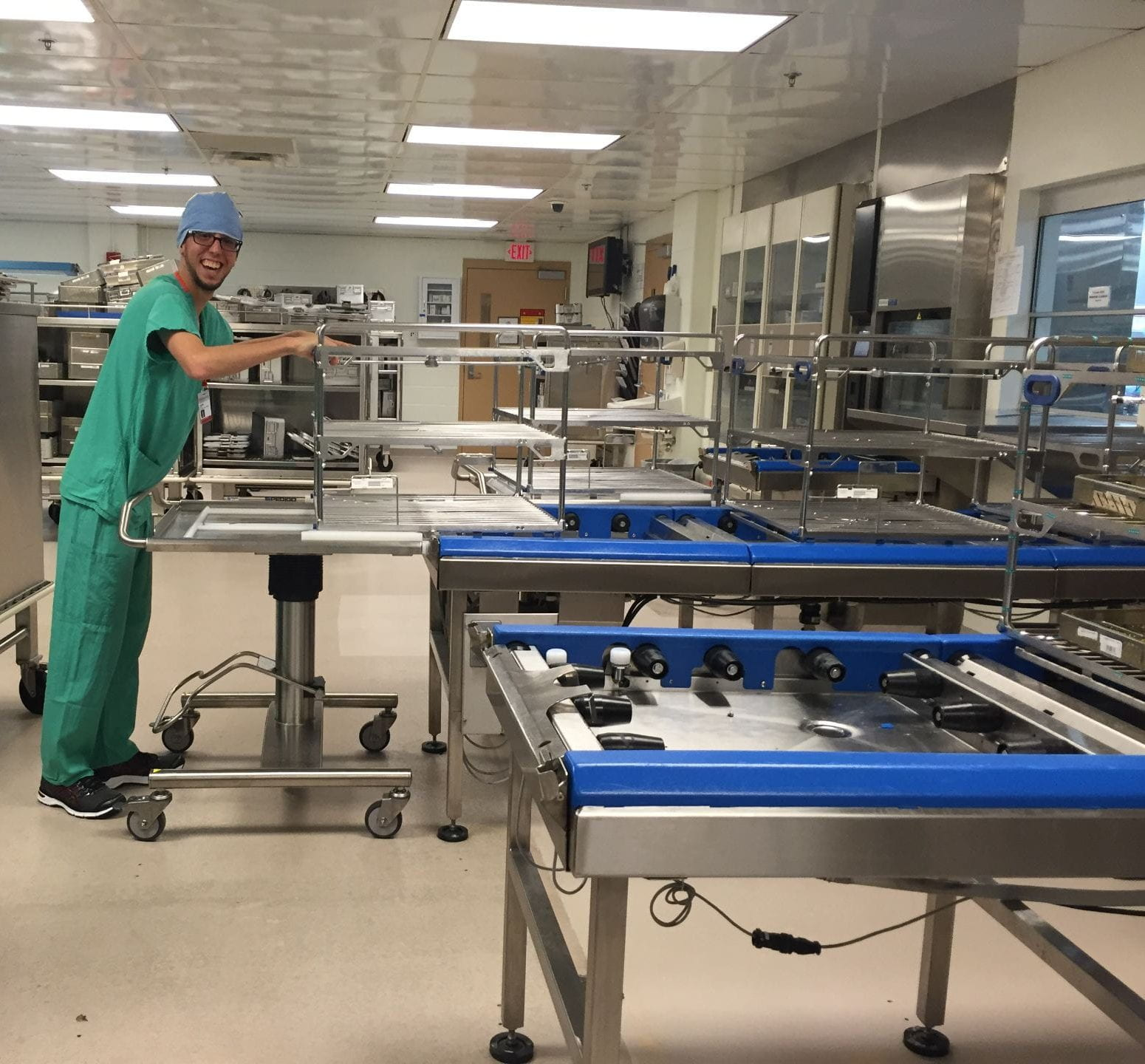 Austin putting a sterilization rack back on the belt in Central Sterile Supplyl