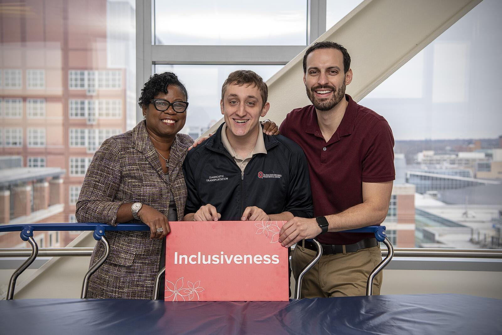 "Ben and his two supervisors smiling in front of a patient transportation cart. They are holding a red sign that says ""Inclusiveness"""