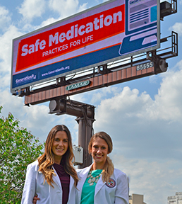 Photo of Generation RX Co-presidents Marie and Emily in front of their billboard