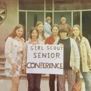 a group of girls holding a sign