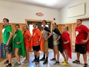 teenagers in a line wearing capes