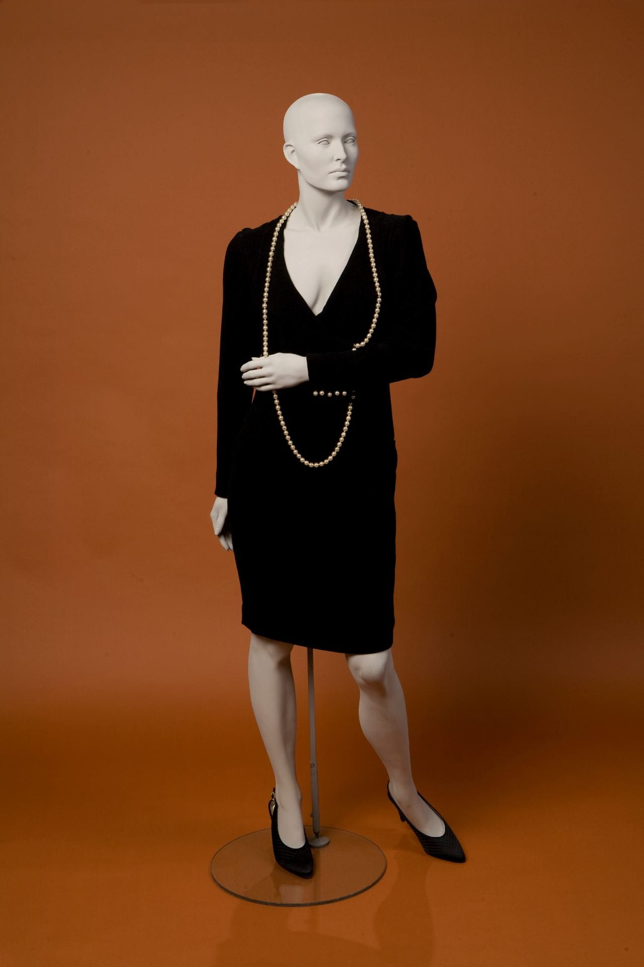 04a520e00f11e6 To the left is a short black wool crepe Chanel dress created by Karl  Lagerfeld.