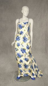 1956 through 1959 Luis Estevez gown. Off-white silk dress with large shaded blue flowers and green leaves. Low V back with a full back that is gathered and draped at the center to form a train.