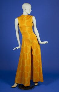 mannequin wearing sleeveless jump suit of yellow with large orange polka dots; pants have wide legs