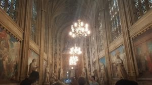 A picture of one of the halls in the British Parliament building. there are chandalier and art on the walls, where are very ornate