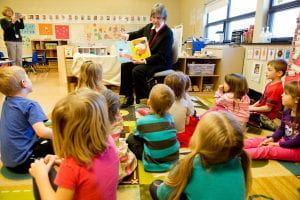 Volunteer reading a story to the children