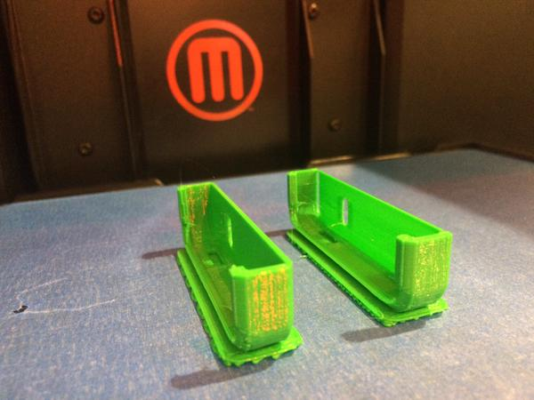 Two halves of an iPhone 5s case printed in green PLA. Makerbot logo, red M inside a red circle, in the background.