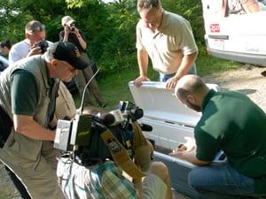 volunteers showing specimens to news crew