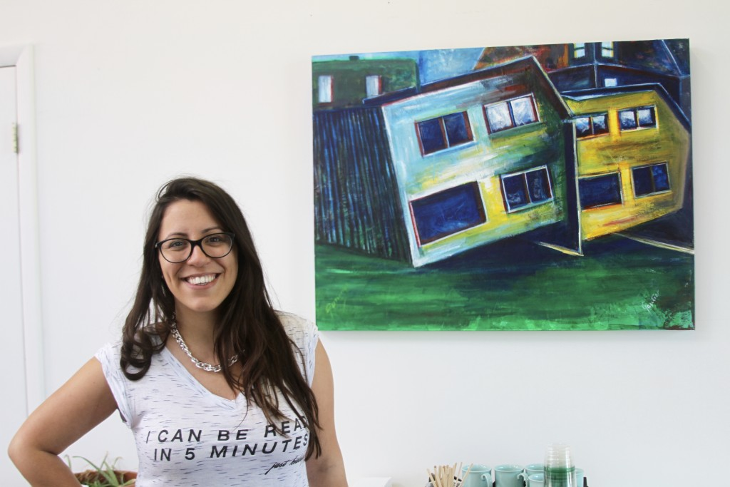 Virginia Nunes Gutierrez stands in front of a painting - done by her uncle during Independent's Day 2015. It is a nod to the two houses once on the site of Bottoms Up - overturned by the great flood of 1913.