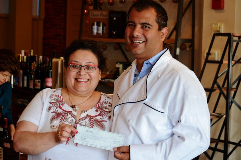 Omar D'Angelo and Project Limitless (through Barroluco Argentine Comfort Food) presents Lair Marcum of Latina Mentoring Academy with funds to support the program (photo courtesy Omar D'Angelo).